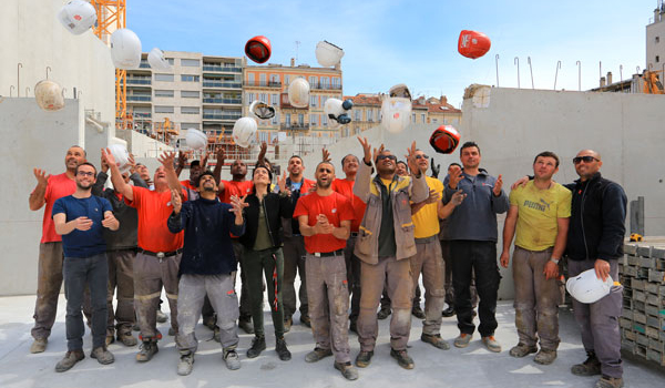 Collaborateurs sur chantier jetant leurs casques en l'air